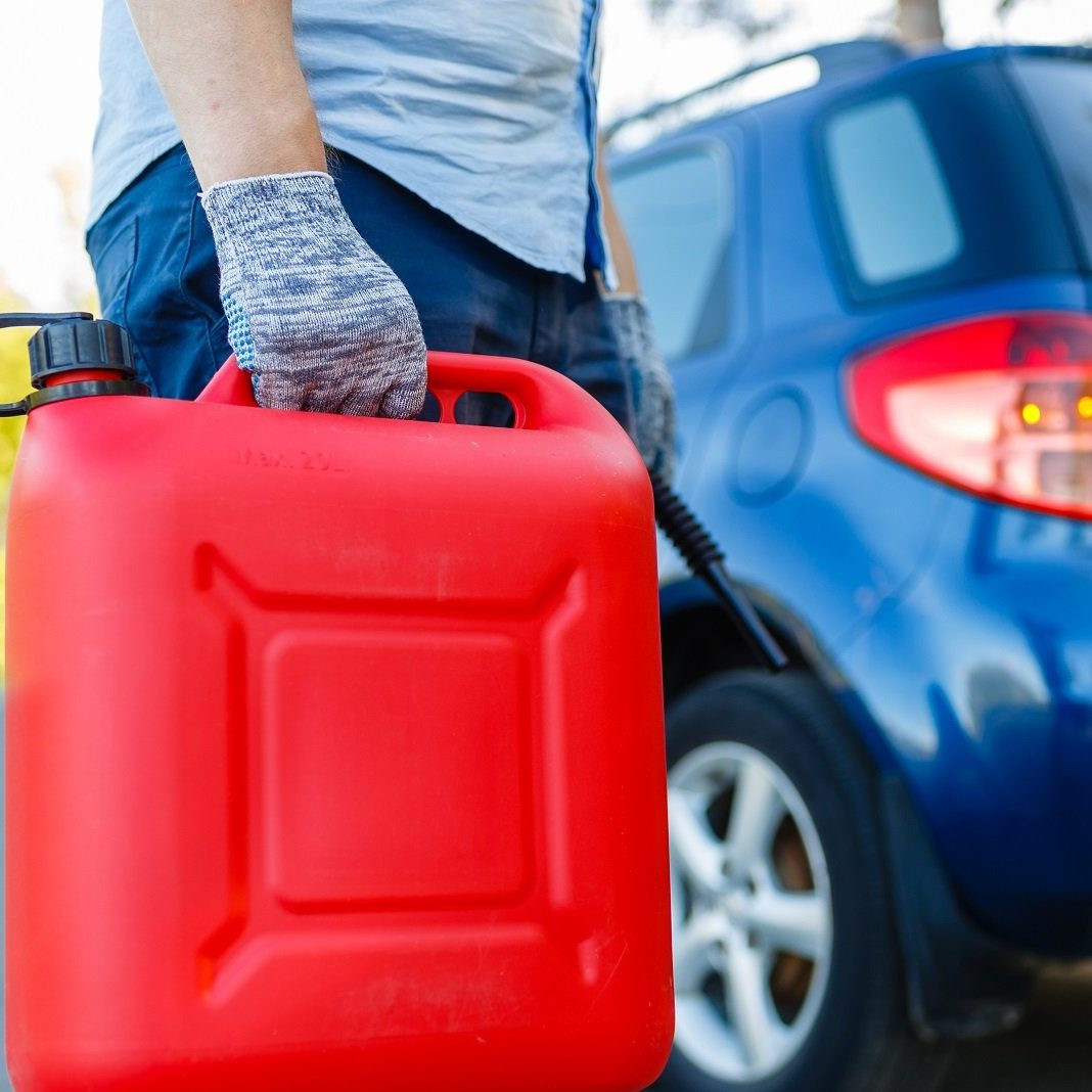Man with a gas can on the side of the road with his car in background, close-up without a face. Driver with refuel canister of fuel on background of stalled car . Concept of empty fuel tank
